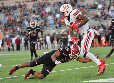 LAS CRUCES, NEW MEXICO - OCTOBER 05, 2019:  Wide receiver Antonio Gandy-Golden #11 of the Liberty Flames gets through a tackle from defensive back Jason Simmons Jr. #17 of the New Mexico State Aggies during their game at Aggie Memorial Stadium on October 05, 2019 in Las Cruces, New Mexico. The Flames defeated the Aggies 20-13.  (Photo by Sam Wasson)