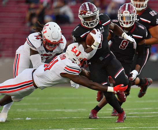 LAS CRUCES, NEW MEXICO - OCTOBER 05, 2019:  Running back Jason Huntley #1 of the New Mexico State Aggies runs against safety Elijah Benton #31 of the Liberty Flames during their game at Aggie Memorial Stadium on October 05, 2019 in Las Cruces, New Mexico.  The Flames defeated the Aggies 20-13.  (Photo by Sam Wasson)