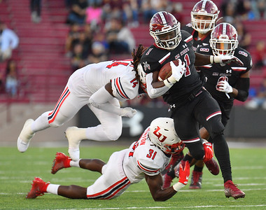 LAS CRUCES, NEW MEXICO - OCTOBER 05, 2019:  Running back Jason Huntley #1 of the New Mexico State Aggies breaks through a tackle from safety Elijah Benton #31 of the Liberty Flames during their game at Aggie Memorial Stadium on October 05, 2019 in Las Cruces, New Mexico. The Flames defeated the Aggies 20-13.  (Photo by Sam Wasson)