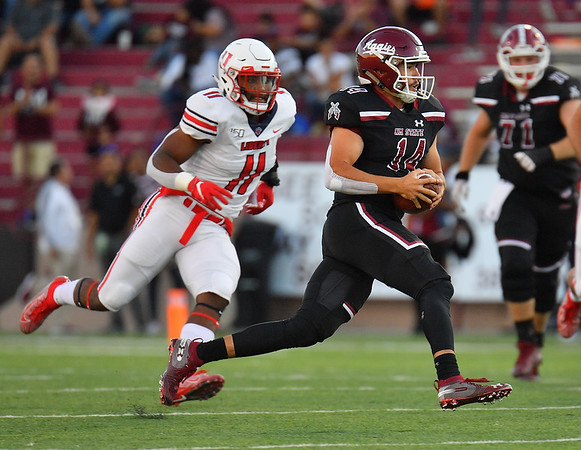 LAS CRUCES, NEW MEXICO - OCTOBER 05, 2019:  quarterback Josh Adkins #14 of the New Mexico State Aggies runs for a gain against defensive lineman Jessie Lemonier #11 of the Liberty Flames during their game at Aggie Memorial Stadium on October 05, 2019 in Las Cruces, New Mexico. The Flames defeated the Aggies 20-13.  (Photo by Sam Wasson)