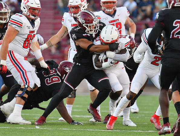 LAS CRUCES, NEW MEXICO - OCTOBER 05, 2019:  Linebacker Javahn Fergurson #7 of the New Mexico State Aggies tackles running back Frankie Hickson #23 of the Liberty Flames during their game at Aggie Memorial Stadium on October 05, 2019 in Las Cruces, New Mexico.  The Flames defeated the Aggies 20-13.  (Photo by Sam Wasson)