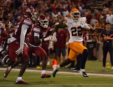 LAS CRUCES, NEW MEXICO - AUGUST 28:  Running back Ronald Awatt #22 of the UTEP Miners runs for a touchdown against defensive back Caleb Mills #12 and defensive back D.J. McCullough #7 of the New Mexico State Aggies in the first half of their game at Aggie Memorial Stadium on August 28, 2016 in Las Cruces, New Mexico.  (Photo by Sam Wasson/bleedCrimson.net)