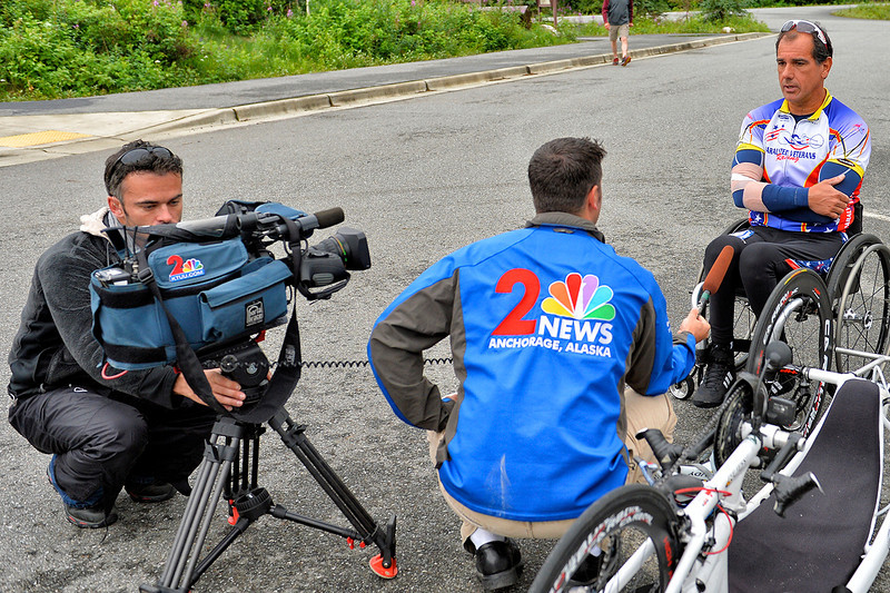 July 20, 2013: Sadler's Alaska Challenge Stage Six from Denali View South to Talkeetna Alaskan Lodge. Charlie Sokaitis from KTUU Anchorage interviews Carlos Moleda (Bluffton, S.C.) before the start of stage six. Moleda finished the 49.4-mile stage in 2:12:09.