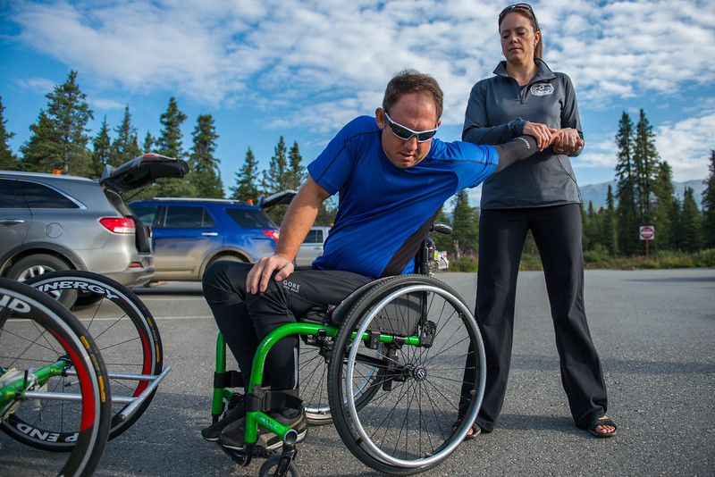 July 25, 2015: Ryan Kelling gets stretched out by race volunteer Teresa Knowles before the start of stage five of the 2015 Alaska Challenge handcycle race.