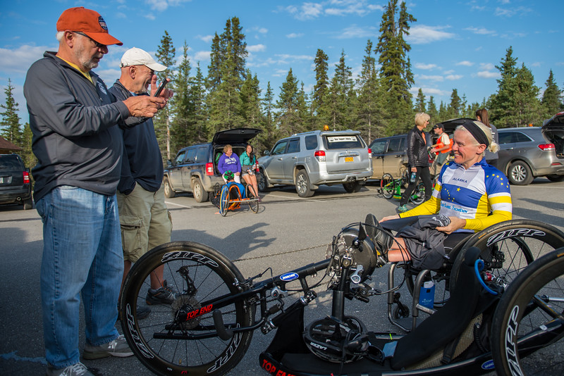 July 25, 2015: Family members of Ashli Molinero chat with her before the start of stage five of the 2015 Alaska Challenge handcycle race.