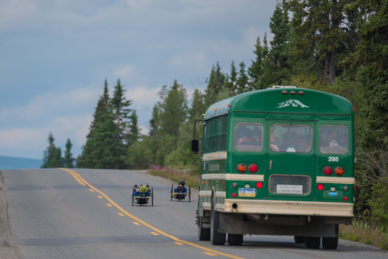 July 25, 2015: A pair of racers are followed by a Park Service bus during stage five of the 2015 Alaska Challenge handcycle race.