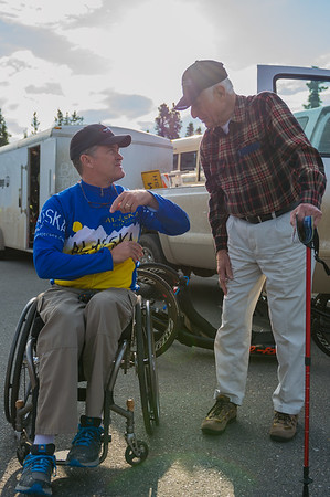 July 25, 2015: Race volunteer Jody Shiflett, an organizer of the Paralyzed Veterans Racing Team, talks with Air Force veteran Joseph Tatusko, who was stationed in Alaska from 1955 to 1958, before the start of stage five of the 2015 Alaska Challenge handcycle race.