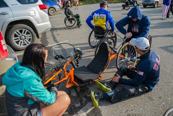 July 25, 2015: Racers work on their bikes before the start of stage five of the 2015 Alaska Challenge handcycle race.