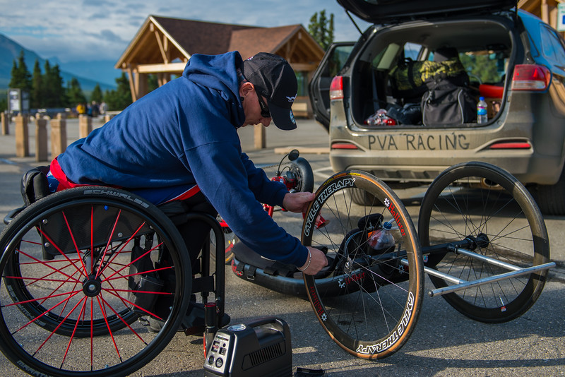 July 25, 2015: Kenny Herriot works on his bike before the starts of stage five of the 2015 Alaska Challenge handcycle race.