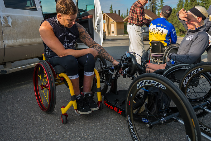 July 25, 2015: Anthony Pedeferri assists Ashli Molinero with her bike stage five of the 2015 Alaska Challenge handcycle race.