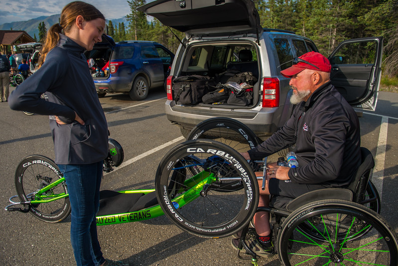 July 25, 2015: Keith Winchell and race volunteer Aubre Adams chat before the start of stage five of the 2015 Alaska Challenge handcycle race.