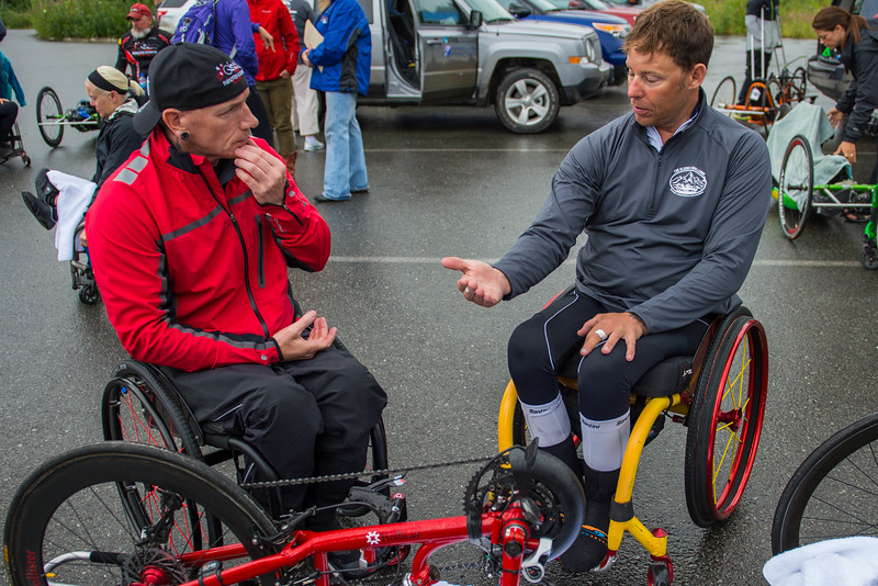 July 26, 2015: Anthony Pedeferri (right) and Kenny Herriot (left) discuss their bike equipment before the start of stage seven of the 2015 Alaska Challenge handcycle race.