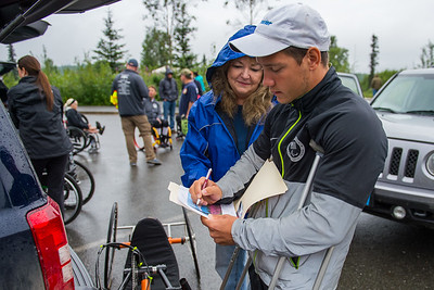 July 26, 2015: Andrew Kurka signs an autograph for a fan before the start of stage seven of the 2015 Alaska Challenge handcycle race.