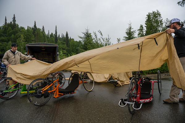July 26, 2015: Race volunteers cover the bikes to keep them dry from the rain before the start of stage seven of the 2015 Alaska Challenge handcycle race.