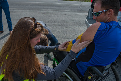 July 25, 2015: Race medic Jenn Adams applies KT Tape to Ryan Kelling before the start of stage six of the 2015 Alaska Challenge handcycle race.