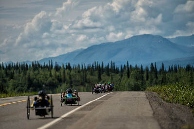 July 25, 2015: A group of racers head off along the Parks Highway following the start of stage six of the 2015 Alaska Challenge handcycle race.