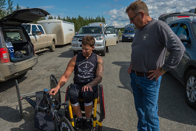 July 25, 2015: Anthony Pedeferri examines his bike before the start of stage six of the 2015 Alaska Challenge handcycle race.