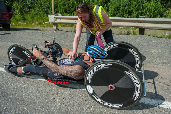 July 25, 2015: Race medic Jenn Adams cools down Anthony Pedeferii with a chunk of ice during stage six of the 2015 Alaska Challenge handcycle race.