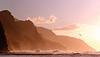 Receding headlands of Kauai coastline illuminated at sunset over a stormy sea with a distant bird