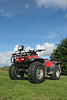 Four wheel drive quad bike standing idle on the grass with a blue sky and clouds to the rear.