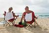 Couple sitting in folding chairs at beautiful Waikiki Beach, Honolulu, Hawaii.