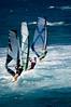 A line of three windsurfers off the coast of Maui