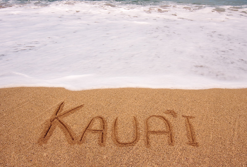 White foam of the tide coming towards the name Kauai scratched in the sand