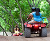 People having fun riding ATVs through a tropical setting