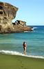 Young woman on a green sand beach on Big Isaland, Hawaii