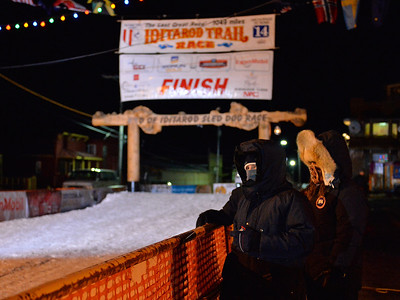 March 10, 2014: A pair of spectators patiently away await the finishers to arrive on Front Street in Nome, Alaska.