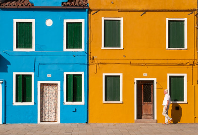 Man Passes Brightly Painted Houses, Piazza Baldassarre Galuppi, Burano, Venice, Veneto, Italy