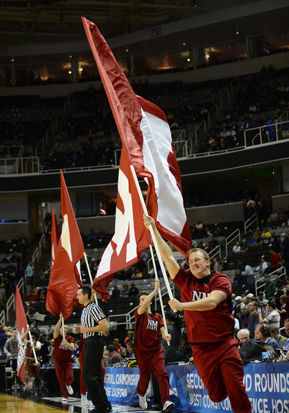 March 21, 2013: Members of the New Mexico State Aggies cheerleading team run out with their flags during a game between the New Mexico State Aggies and the Saint Louis Billikens in the second round of the NCAA Division I Men's Basketball Championship at HP Pavilion in San Jose, California.