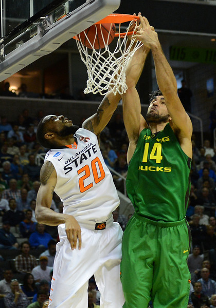 March 21, 2013: Oregon Ducks forward Arsalan Kazemi (14) dunks over Oklahoma State Cowboys forward Michael Cobbins (20) during a game between the Oregon Ducks and the Oklahoma State Cowboys in the second round of the NCAA Division I Men's Basketball Championship at HP Pavilion in San Jose, California.