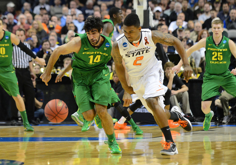 March 21, 2013: Oregon Ducks forward Arsalan Kazemi (14) and Oklahoma State Cowboys guard/forward Le'Bryan Nash (2) chase down a loose ball during a game between the Oregon Ducks and the Oklahoma State Cowboys in the second round of the NCAA Division I Men's Basketball Championship at HP Pavilion in San Jose, California.