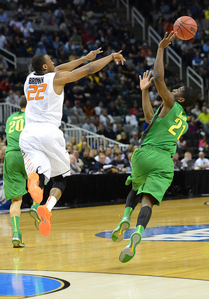 March 21, 2013: Oklahoma State Cowboys guard Markel Brown (22) passes the ball over the outstretched arm of Oregon Ducks guard Damyean Dotson (21) during a game between the Oregon Ducks and the Oklahoma State Cowboys in the second round of the NCAA Division I Men's Basketball Championship at HP Pavilion in San Jose, California.