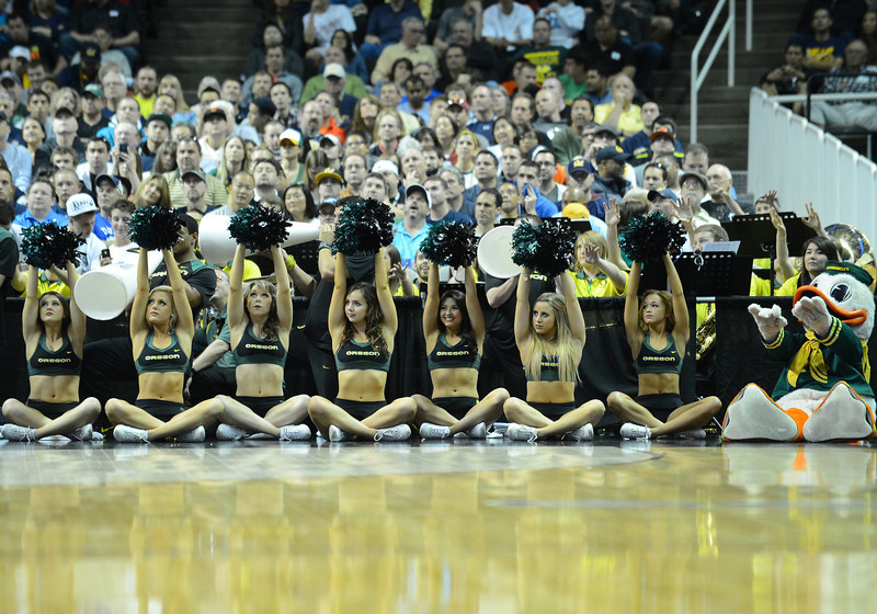 March 23, 2013: Oregon Ducks cheerleaders raise their poms while an Oregon Ducks player shoots a free throw during a game between the Oregon Ducks and the Saint Louis Billikens in the third round of the NCAA Division I Men's Basketball Championship at HP Pavilion in San Jose, California.