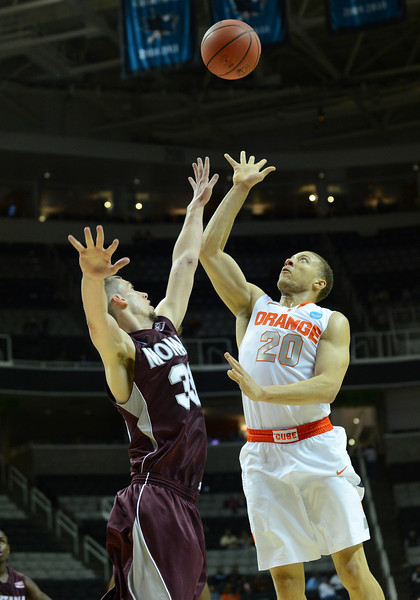 March 21, 2013: Syracuse Orange guard Brandon Triche (20) floats a shot over the defense of Montana Grizzlies forward Mike Weisner (33) during a game between the Syracuse Orangemen and the Montana Grizzlies in the second round of the NCAA Division I Men's Basketball Championship at HP Pavilion in San Jose, California.
