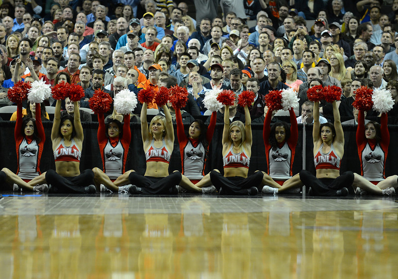 March 21, 2013: UNLV Rebels cheerleaders raise their pom poms during a free throw during a game between the UNLV Rebels and the Cal Golden Bears in the second round of the NCAA Division I Men's Basketball Championship at HP Pavilion in San Jose, California.