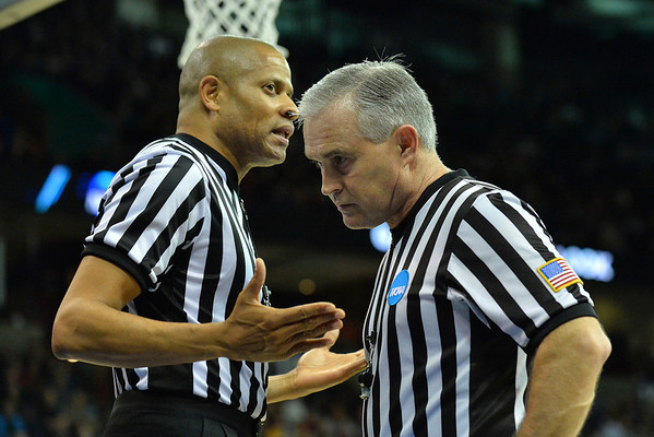 March 20, 2014: A pair of officials talk during a second round game of the NCAA Division I Men's Basketball Championship between the 5-seed Cincinnati Bearcats and the 12-seed Harvard Crimson at Spokane Arena in Spokane, Wash. Harvard defeated Cincinnati 61-57.