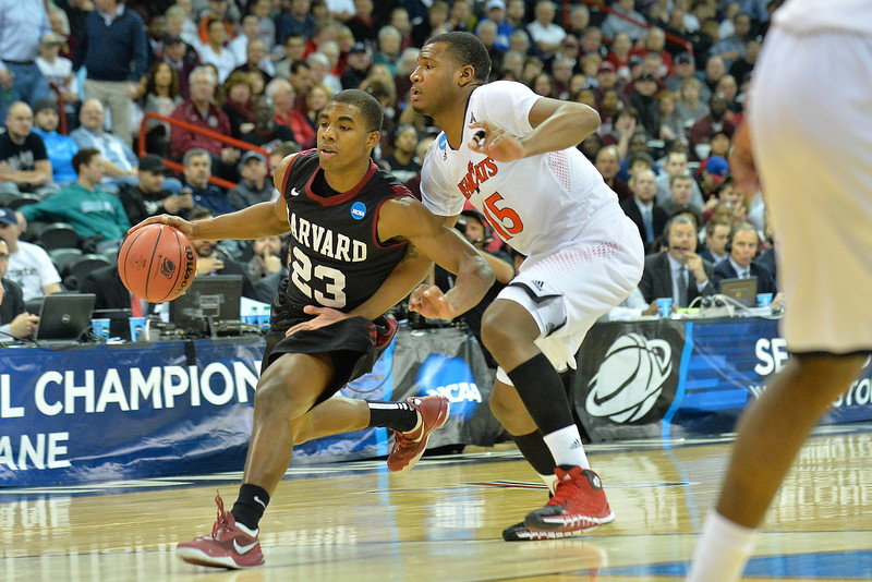 March 20, 2014: Harvard Crimson guard/forward Wesley Saunders (23) drives past Cincinnati Bearcats forward Jermaine Sanders (15) during a second round game of the NCAA Division I Men's Basketball Championship between the 5-seed Cincinnati Bearcats and the 12-seed Harvard Crimson at Spokane Arena in Spokane, Wash. Harvard defeated Cincinnati 61-57.