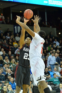 March 20, 2014: Harvard Crimson guard/forward Wesley Saunders (23) shoots over Cincinnati Bearcats forward Jermaine Sanders (15) during a second round game of the NCAA Division I Men's Basketball Championship between the 5-seed Cincinnati Bearcats and the 12-seed Harvard Crimson at Spokane Arena in Spokane, Wash. Harvard defeated Cincinnati 61-57.