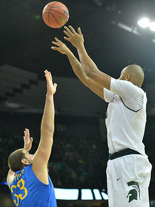 March 20, 2014: Michigan State Spartans forward Adreian Payne (5) shoots over Delaware Fightin' Blue Hens forward Carl Baptiste (33) during a second round game of the NCAA Division I Men's Basketball Championship between the 4-seed Michigan State and the 13-seed Delaware at Spokane Arena in Spokane, Wash. Michigan State defeated Delaware 93-78.