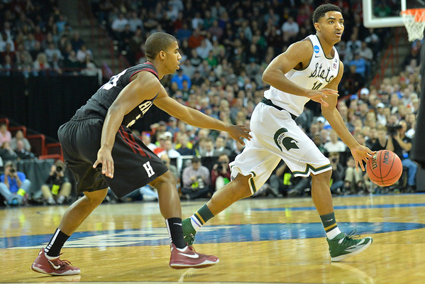 March 22, 2014: Michigan State Spartans guard Gary Harris (14) is guarded by Harvard Crimson guard/forward Wesley Saunders (23) during a third round game of the NCAA Division I Men's Basketball Championship between the 4-seed Michigan State and the 12-seed Harvard at Spokane Arena in Spokane, Wash. Michigan State defeated Harvard 80-73 to advance to the Sweet Sixteen.