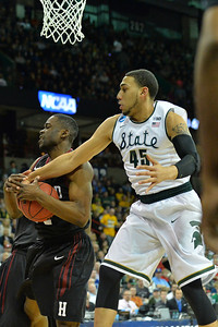 March 22, 2014: Harvard Crimson forward Steve Moundou-Missi (14) and Michigan State Spartans guard Denzel Valentine (45) battle for a rebound during a third round game of the NCAA Division I Men's Basketball Championship between the 4-seed Michigan State and the 12-seed Harvard at Spokane Arena in Spokane, Wash. Michigan State defeated Harvard 80-73 to advance to the Sweet Sixteen.