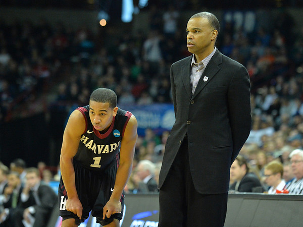 March 22, 2014: Harvard Crimson head coach Tommy Amaker and Harvard Crimson guard Siyani Chambers (1) talk in a timeout during a third round game of the NCAA Division I Men's Basketball Championship between the 4-seed Michigan State and the 12-seed Harvard at Spokane Arena in Spokane, Wash. Michigan State defeated Harvard 80-73 to advance to the Sweet Sixteen.