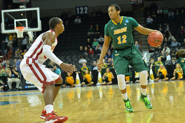 March 20, 2014: North Dakota State Bison guard Lawrence Alexander (12) surveys the defense during a second round game of the NCAA Division I Men's Basketball Championship between the 5-seed Oklahoma and the 12-seed North Dakota State at Spokane Arena in Spokane, Wash. North Dakota State defeated Oklahoma 80-75 in overtime.