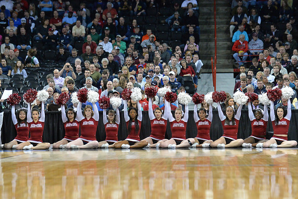 March 20, 2014: Harvard Crimson cheerleaders raise their pons during a free throw during a second round game of the NCAA Division I Men's Basketball Championship between the 5-seed Cincinnati Bearcats and the 12-seed Harvard Crimson at Spokane Arena in Spokane, Wash. Harvard defeated Cincinnati 61-57.