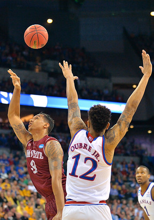 March 20, 2015: New Mexico State Aggies forward Remi Barry (3) puts up a shot around the defense of Kansas Jayhawks guard Kelly Oubre Jr. (12) during a second round game between No. 2 seed Kansas and No. 15 seed New Mexico State in the 2015 NCAA Men's Basketball Championship Tournament at CenturyLink Center in Omaha, Neb. Kansas defeated New Mexico State 76-57. Kansas defeated New Mexico State 76-57. Kansas defeated New Mexico State 76-57.