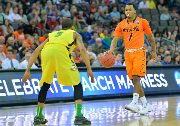 March 20, 2015: Oklahoma State Cowboys guard Tyree Griffin (1) brings the ball up the court against Oregon Ducks guard Casey Benson (2) during a second round game between No. 8 Oregon and No. 9 Oklahoma State in the 2015 NCAA Men's Basketball Championship Tournament at CenturyLink Center in Omaha, Neb. Oregon defeated Oklahoma State 79-73.