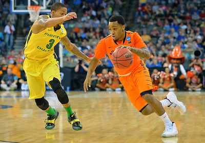 March 20, 2015: Oklahoma State Cowboys guard Tyree Griffin (1) dribbles past Oregon Ducks guard Joseph Young (3) during a second round game between No. 8 Oregon and No. 9 Oklahoma State in the 2015 NCAA Men's Basketball Championship Tournament at CenturyLink Center in Omaha, Neb. Oregon defeated Oklahoma State 79-73.